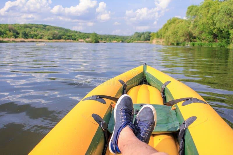 人是在黄色小船的放松河 POV 免版税库存图片