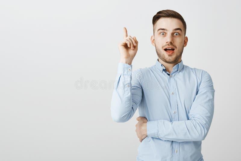 人有分享与队的优良创艺 在提高索引的正式蓝色衬衣的热心激动的悦目男性 免版税库存图片