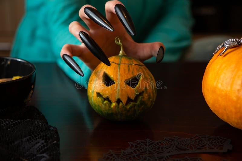 人有坐在木桌上的南瓜起重器的` s手照片  免版税库存照片