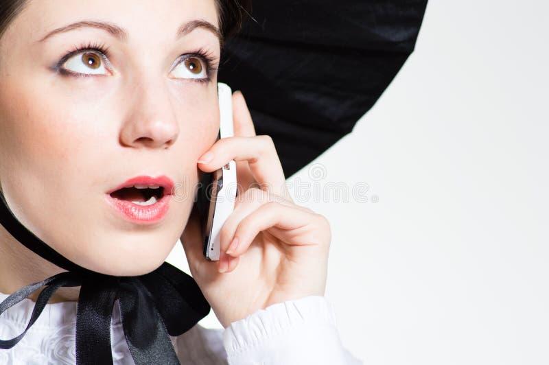 年轻人有手机的惊奇的妇女 免版税库存照片
