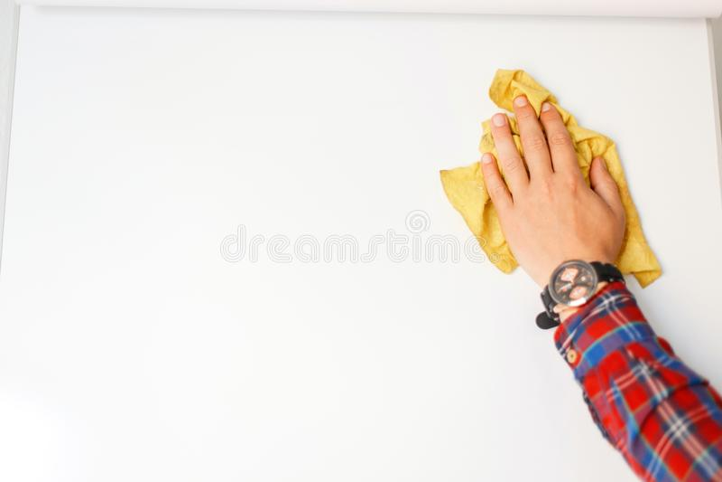 人有旧布的` s手在办公室清洗一个白板 免版税库存照片