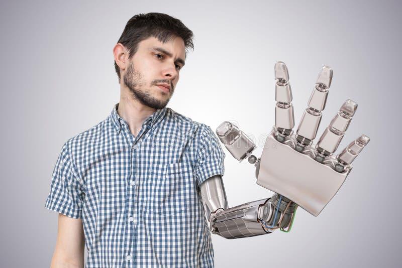 年轻人有机器人手作为他的手的替换 3D回报了手的例证 库存例证