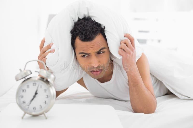 人有枕头的覆盖物耳朵,他在床上看闹钟 图库摄影