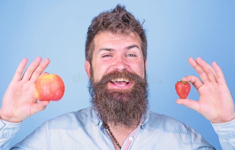 人有胡子微笑拿着苹果和草莓在手蓝色背景中 维生素果子营养概念 医疗保健 免版税图库摄影