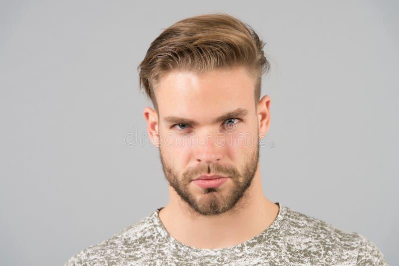 人有胡子的确信的面孔,灰色背景 护肤概念 人有胡子的不剃须的人看起来英俊和穿着考究 免版税图库摄影