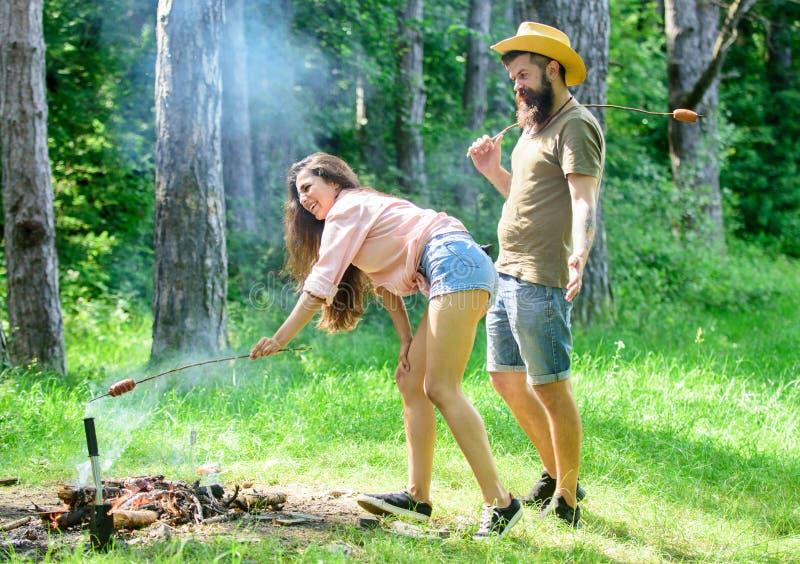 人有胡子的行家看性感的女性屁股 诱人的位置 女孩性感的屁股牛仔布短缺烧烤香肠 免版税库存照片