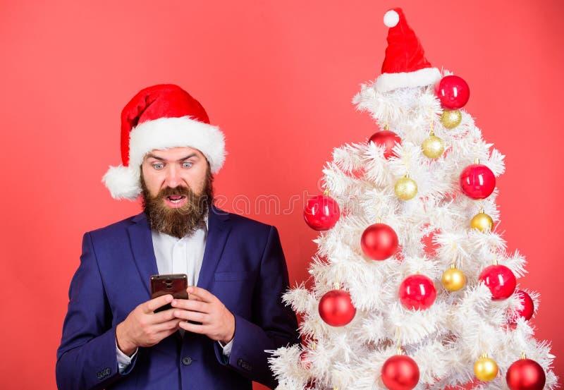 人有胡子的行家穿戴正装和圣诞老人帽子举行智能手机 传送圣诞节招呼的流动信息 短小 图库摄影