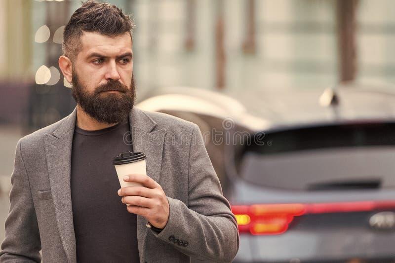 人有胡子的行家饮料咖啡纸杯 穿着考究的商人享受咖啡休息室外都市背景 库存图片