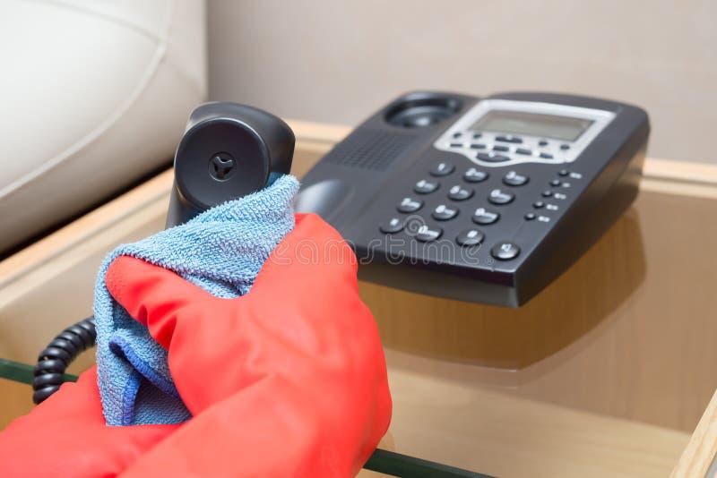 人有蓝色布料的清洁电话 免版税库存图片