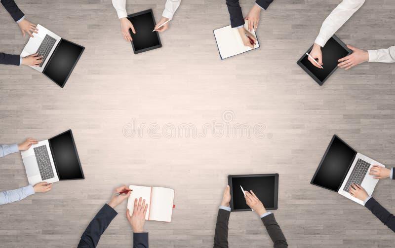 人有设备的在有书桌讨论和研究膝上型计算机,在队的片剂的手上 免版税图库摄影