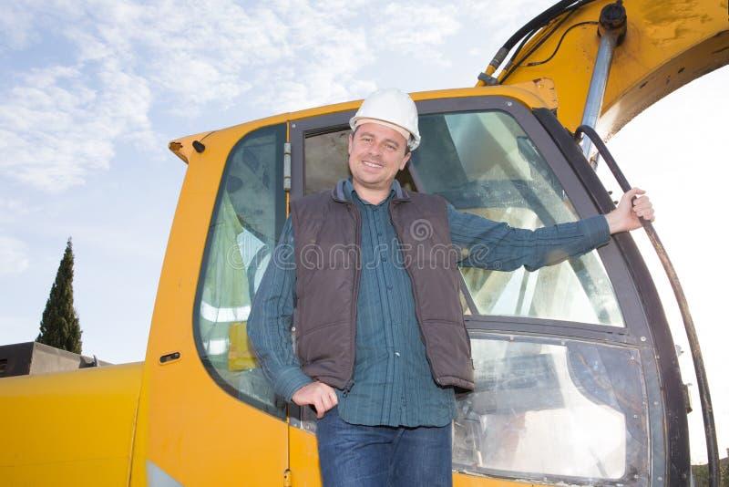 人有黄色挖掘机的司机工作者 免版税库存图片