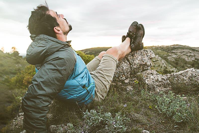 人本质上放松和供以座位的 人观察在山的风景 免版税图库摄影