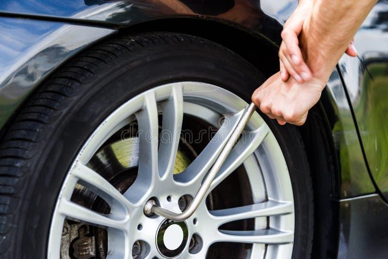 人松开后轮的螺栓汽车更换轮胎 免版税图库摄影