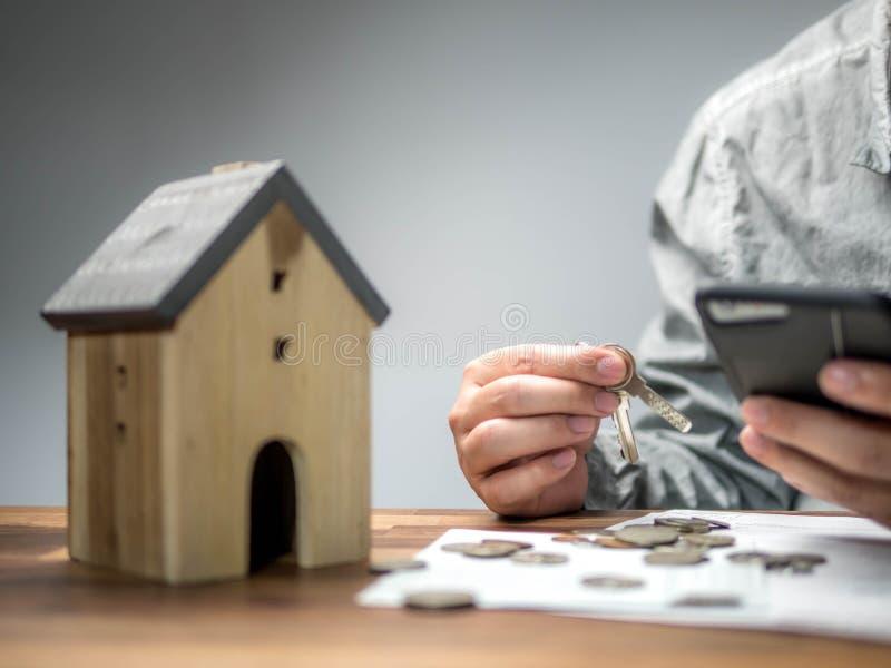 人检查从智能手机的票据和有经济以家庭债务,金钱概念 房地产,买公寓 免版税库存图片