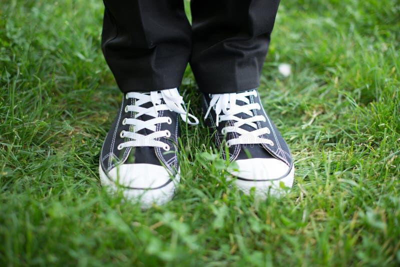 人民在运动鞋的公园脚在绿草在晴天 免版税库存照片