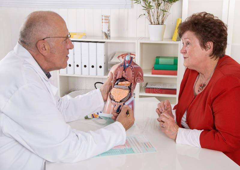 人民医生和患者-谈论健康的资深 库存图片