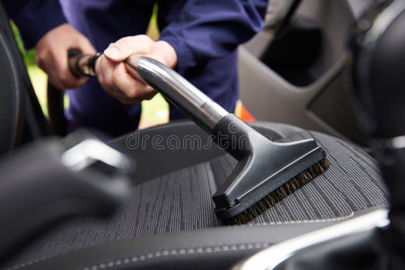 人汽车Hoovering位子在汽车清洁期间的 库存图片