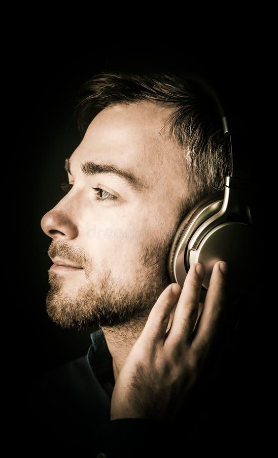 年轻人沉思,他听到音乐 库存照片