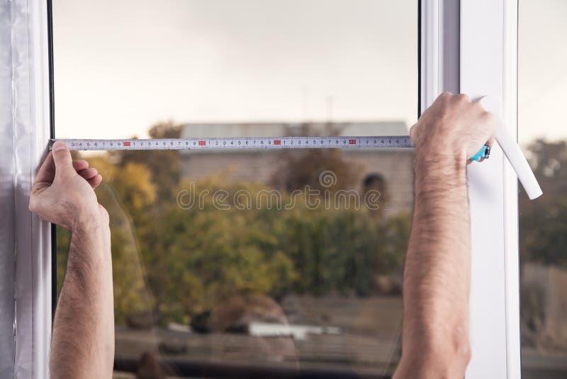 人测量的窗口 安装新窗口在房子 免版税库存图片