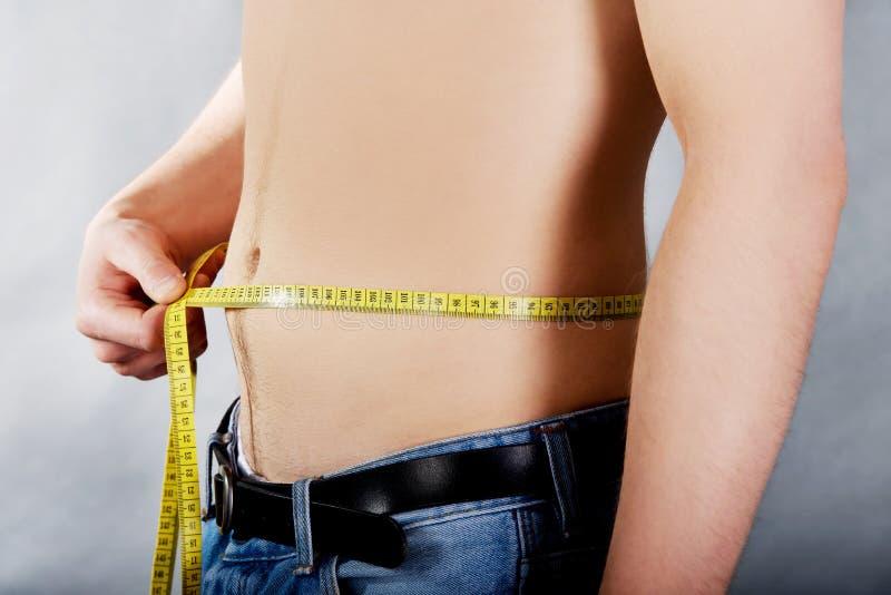年轻人测量的腰部 图库摄影