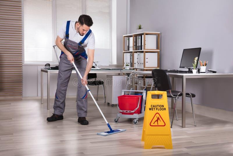 人清洁硬木地板在办公室 图库摄影