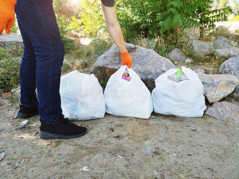 人清除了公园和海滩从残骸 他拿着袋子垃圾和塑料 教的孩子的概念 图库摄影