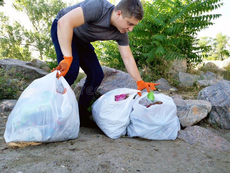 人清除了公园和海滩从残骸 他拿着袋子垃圾和塑料 教的孩子的概念 库存图片