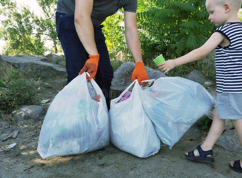 人清除了公园和海滩从残骸 他拿着袋子垃圾和塑料 教的孩子的概念 免版税图库摄影