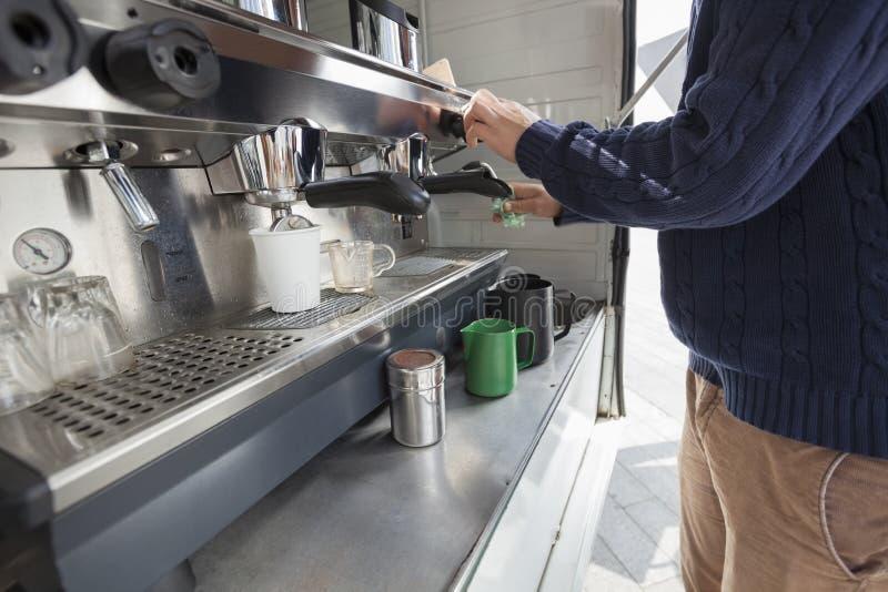 人清洁咖啡机器的中央部位在流动商店 免版税库存图片