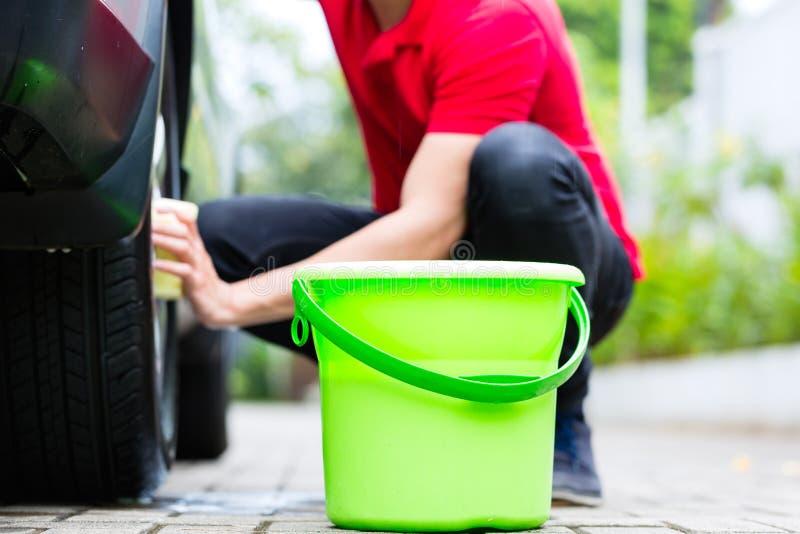 人清洁轮子外缘,当洗车时 库存照片