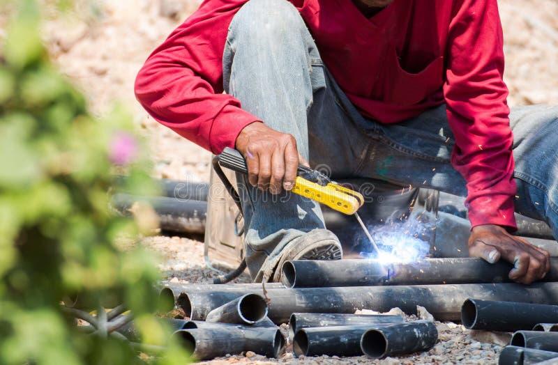 人熟练的运转的工厂焊工,研,钻子 库存照片