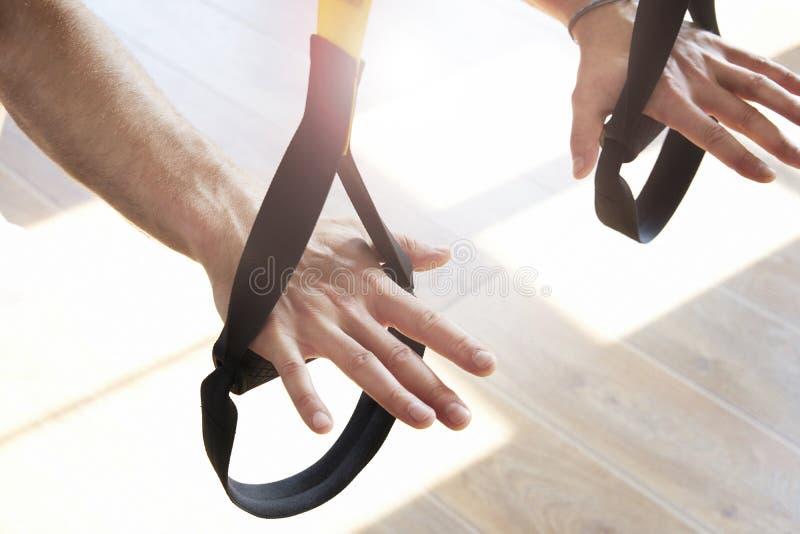 人特写镜头递做单独锻炼与在现代健身房俱乐部,锻炼唯一体育的健身传送带,晒黑发光 免版税库存图片