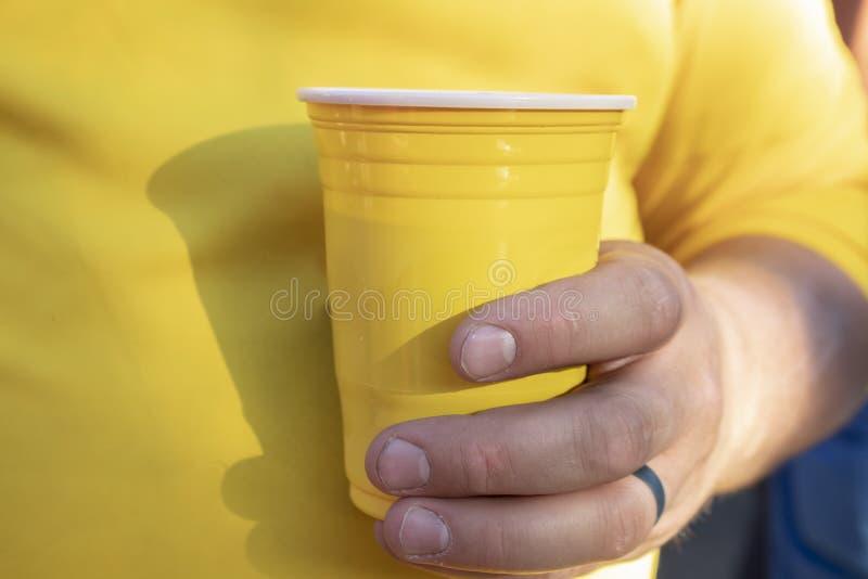 人特写镜头黄色衬衣用工人的手和钉子和拿着黄色塑料水杯- sel的黑结婚戒指的 库存照片