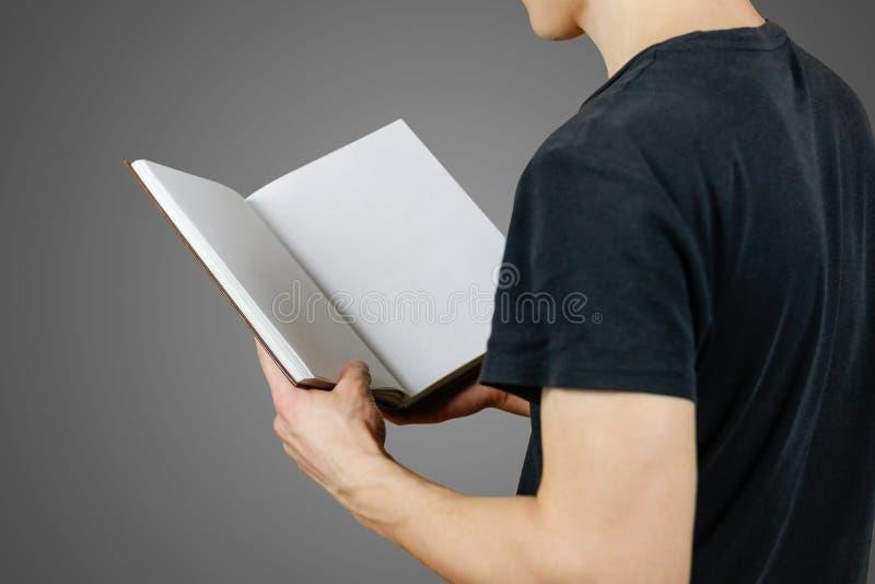 人特写镜头拿着空白开放白皮书的黑T恤杉的  免版税库存照片
