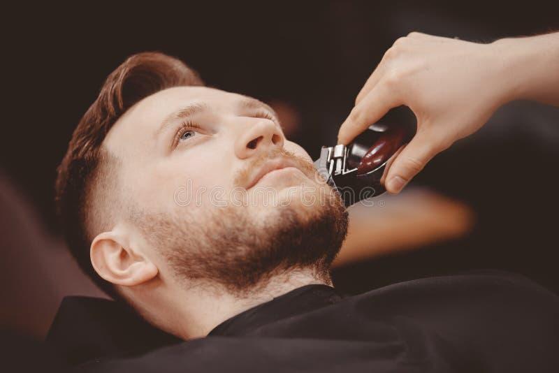 人理发师刮客户胡子椅子理发店的 免版税库存照片