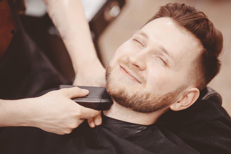 人理发师刮客户胡子椅子理发店的 库存照片