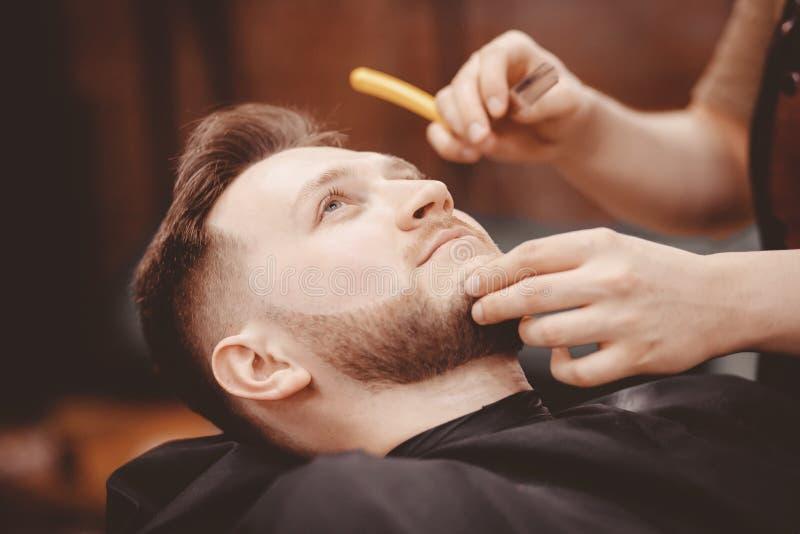 人理发师刮客户胡子椅子理发店的 库存图片