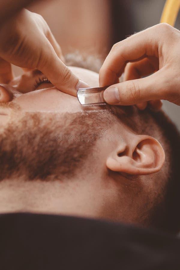 人理发师刮客户胡子椅子理发店的 免版税库存图片
