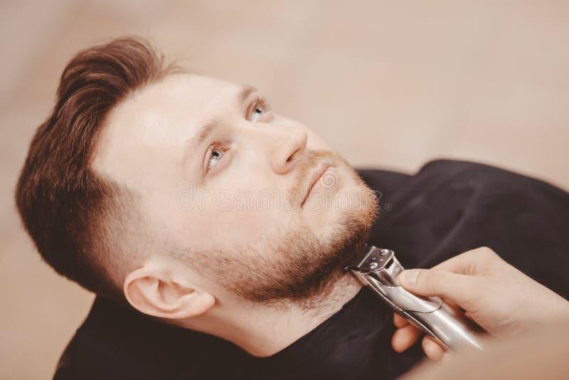 人理发师刮客户胡子椅子理发店的 图库摄影