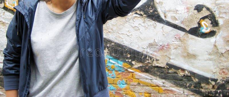 年轻人生活方式画象反对五颜六色的都市砖墙背景的 免版税库存图片