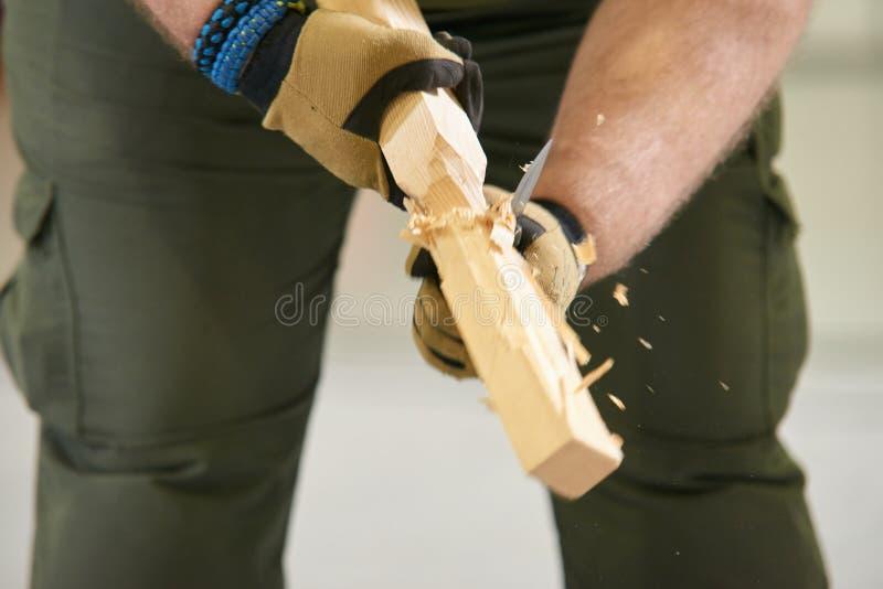 人用一个木酒吧的刀子切开 库存照片