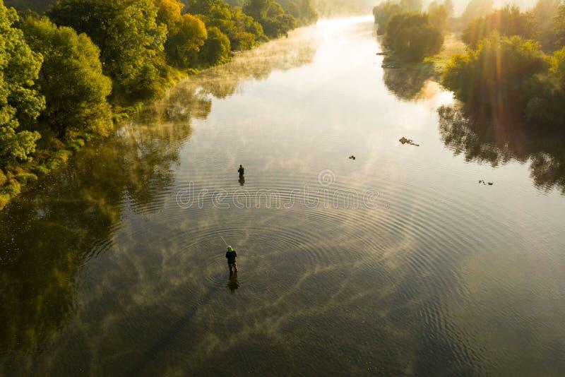 人用假蝇钓鱼的空中射击在一条河早晨夏天 免版税库存照片
