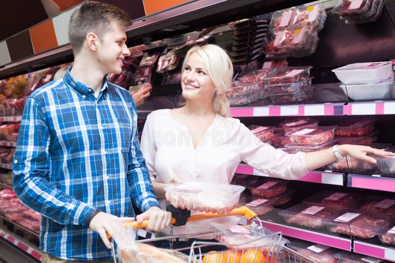年轻人用在a的肉部门的白肤金发的妻子购买肉 免版税图库摄影