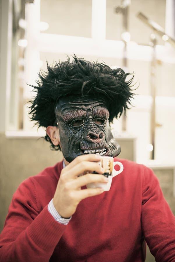 人用大猩猩面具饮用的咖啡 库存照片