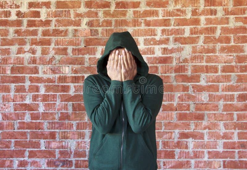 年轻人用有砖墙的手盖他的面孔作为背景 免版税库存照片