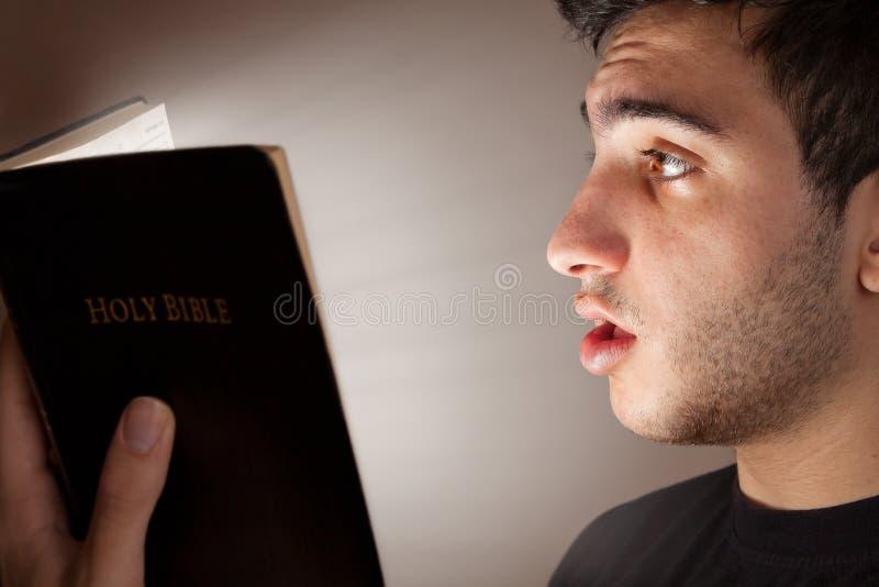 人在触目惊心的读书圣经 免版税库存照片