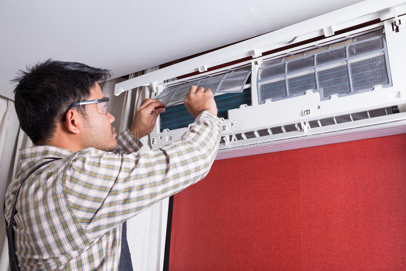 年轻人电工清洁空调在客户房子里 图库摄影