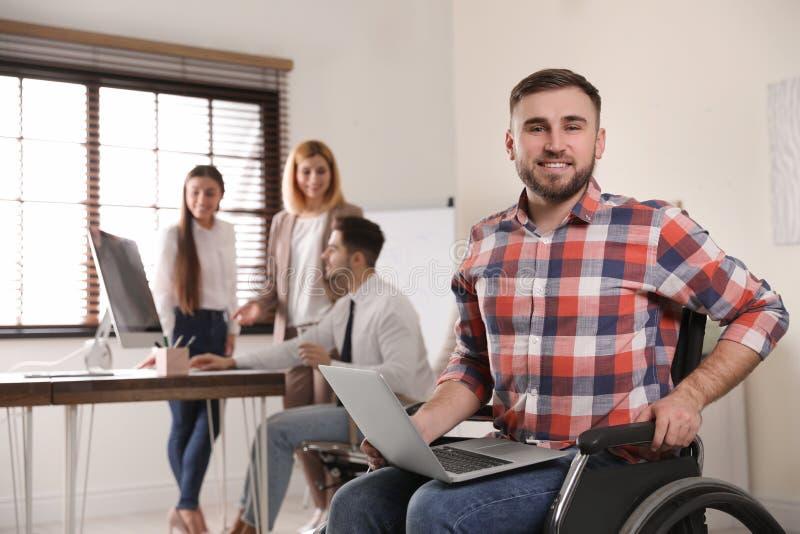 人画象轮椅的有膝上型计算机和他的同事的 库存图片