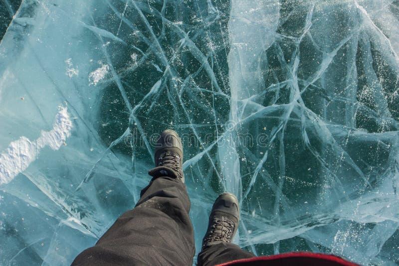 人画象黑长裤和起动鞋子的在冻湖Khovsgol在蒙古 免版税库存图片