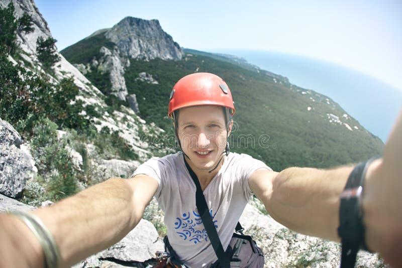 人登山人做与山和海背景的selfie 免版税库存图片